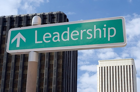 """Street sign with an arrow and the word """"leadership"""" located in a business district."""